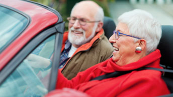 Elderly couple laughing in their car