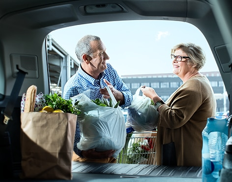 Couple packing groceries into their car