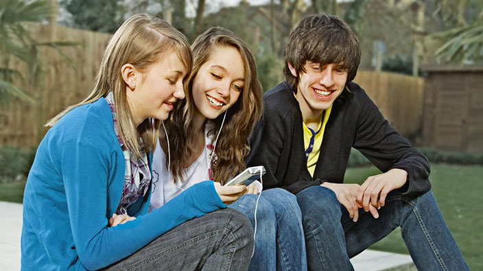 Three teenagers laughing together