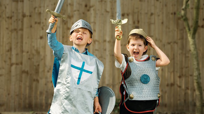 Two children playing dressed as knights