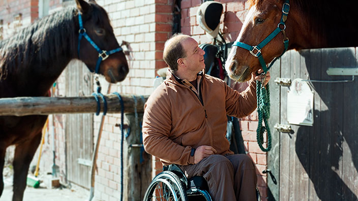 Man in wheelchair petting a horse