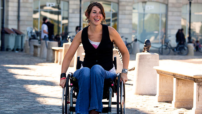 Woman in a wheelchair smiling outside
