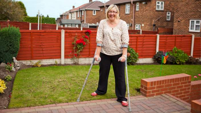 Women with crutches smiling in her backyard