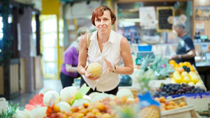 Woman at the grocery store picking fruit