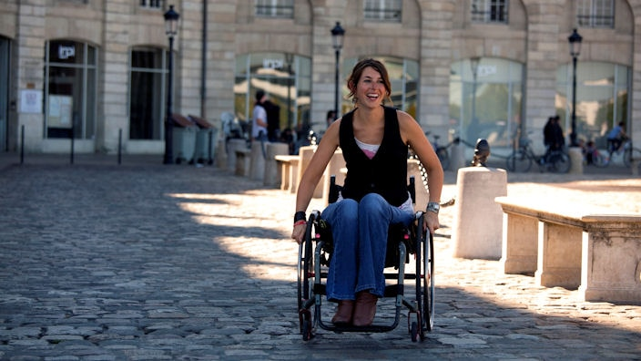 Women in a wheelchair smiling outside
