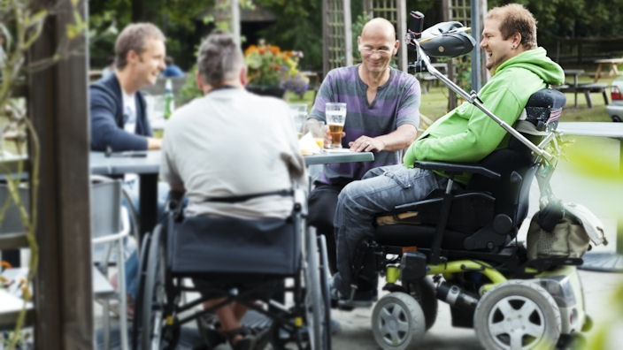 Group of friends in wheelchairs meeting at a pub